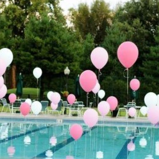Helium filled balloons tied to weights in pool i